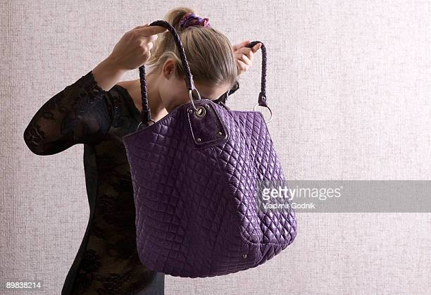 a woman looking into her large purse - borsetta da sera foto e immagini stock
