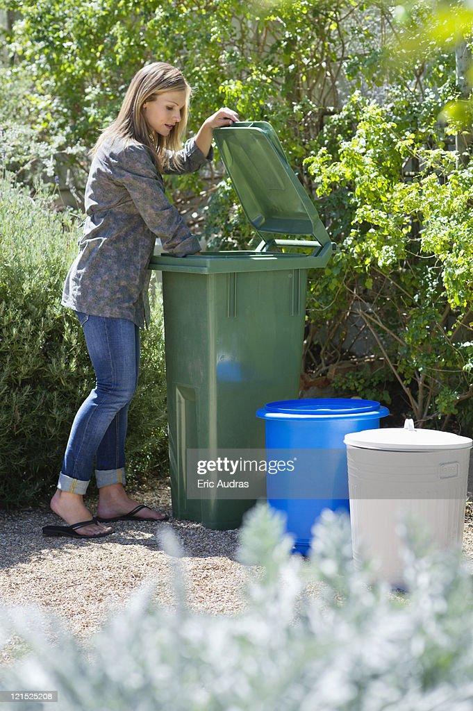 Woman looking into recycling bin : Stock Photo