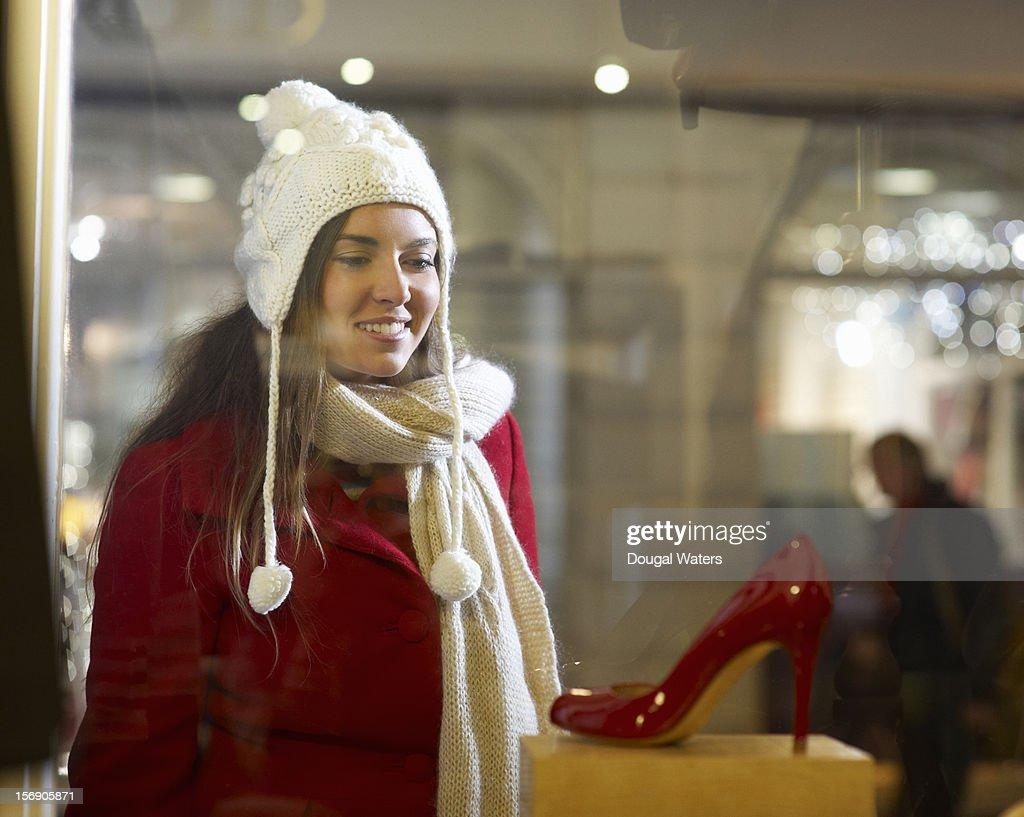 Woman looking into shop window at red shoe. : Foto de stock