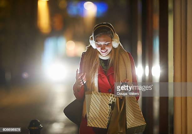 Woman looking into shopping bag on street.