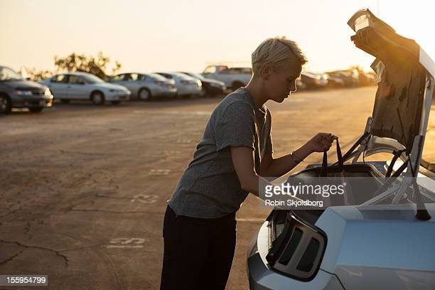 Woman looking into trunk of car