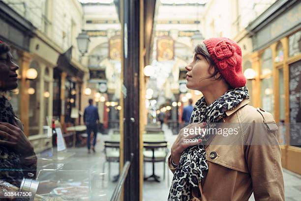 Woman looking into window of traditional store in Paris.