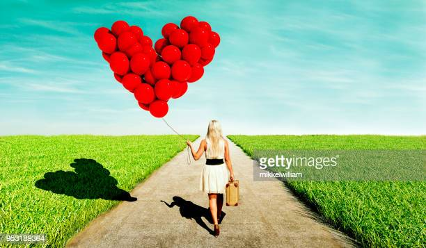 Woman looking love while walking with heart shaped red balloons and a suitcase