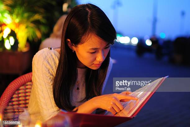 Woman Looking Menu At Restaurant