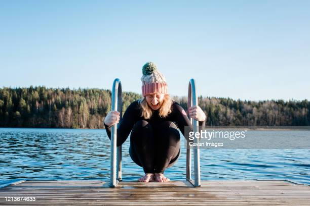 woman looking nervous about cold water ice swimming in sweden - cold temperature stock pictures, royalty-free photos & images