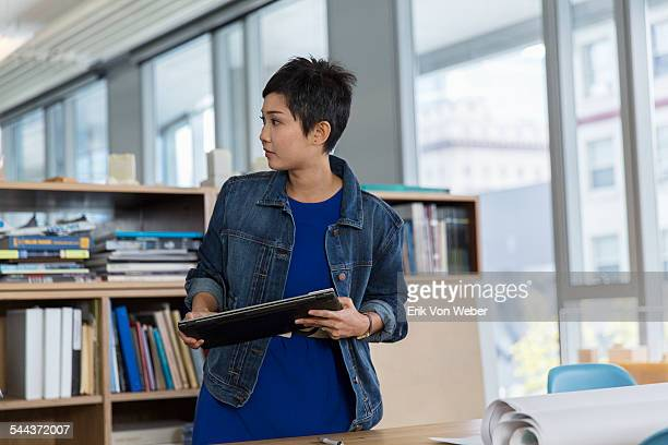 Woman looking off camera holding tablet