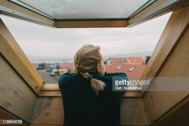 woman looking our of the window on city - nordic countries stock pictures, royalty-free photos & images