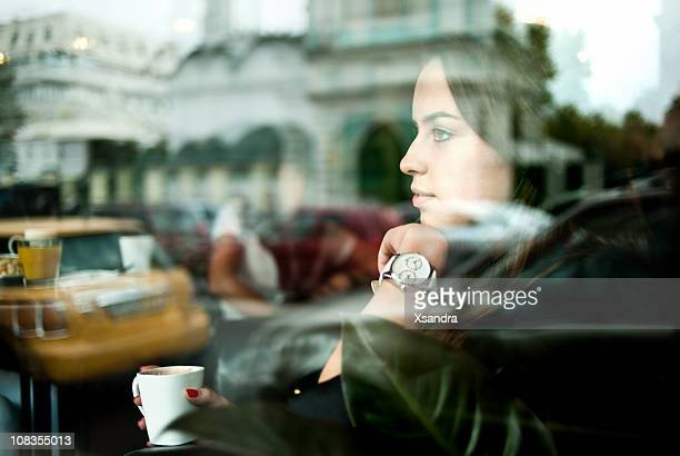 Woman looking out a window in a cafe at a street scene