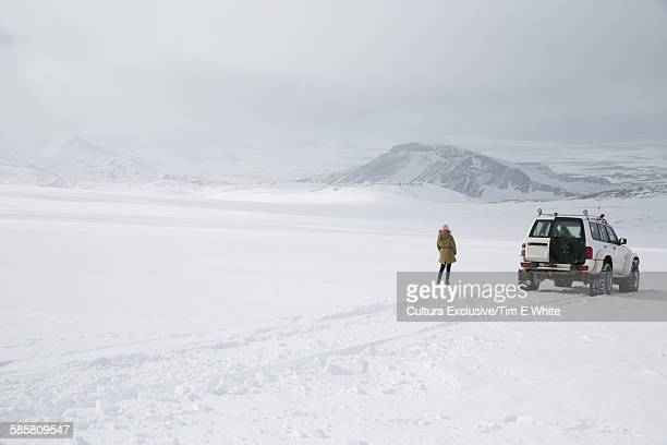 Woman looking out at snow covered landscape, Langjokull glacier, Iceland
