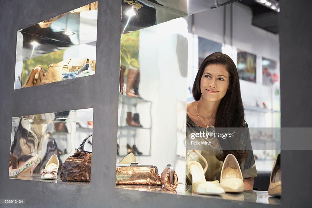 Woman looking out boutique window : Stock Photo