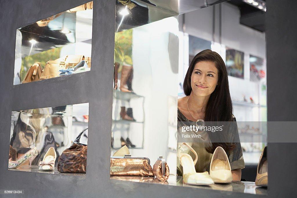 Woman looking out boutique window : Bildbanksbilder