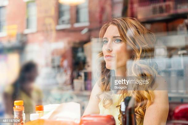 NYC Woman Looking Out Cafe Window with Building Reflections