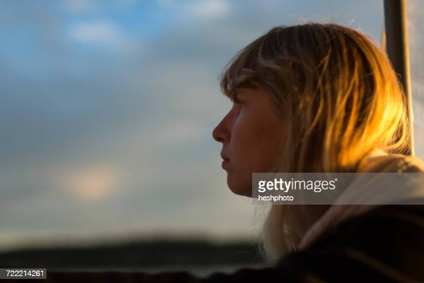 woman looking out from boat at sunset on coast of maine, usa - heshphoto fotografías e imágenes de stock