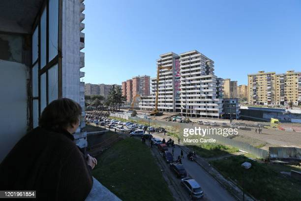 A woman looking out from the building opposite looks at the demolition of the building known as Vela Verde in the Scampia district of Naples The...