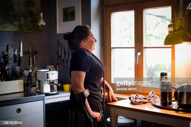 woman looking out her kitchen window - disabilitycollection stock-fotos und bilder