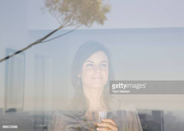 Woman looking out living room window