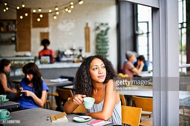woman looking out of a cafe window - differential focus stock pictures, royalty-free photos & images