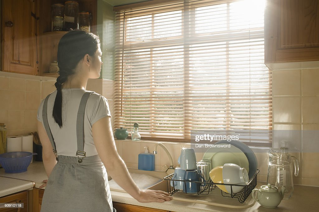 Woman looking out of a window : Stock Photo