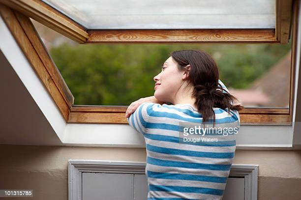 Woman looking out of attic window.