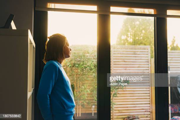 woman looking out of back door at sunset - looking through window stock pictures, royalty-free photos & images