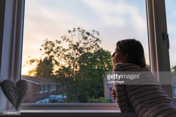 woman looking out of bedroom window at sunset - boredom stock pictures, royalty-free photos & images