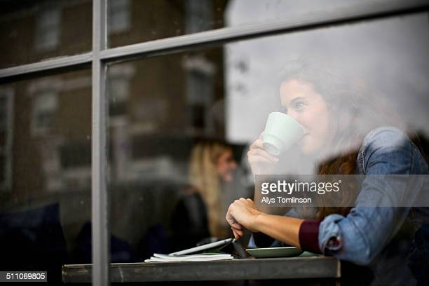 Woman looking out of cafe window