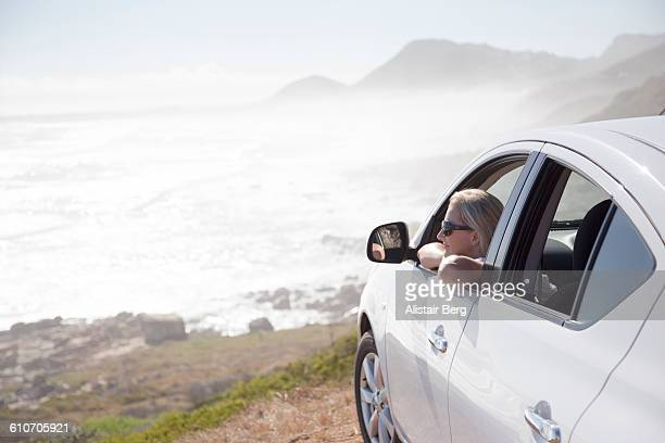 Woman looking out of car overlooking a beach