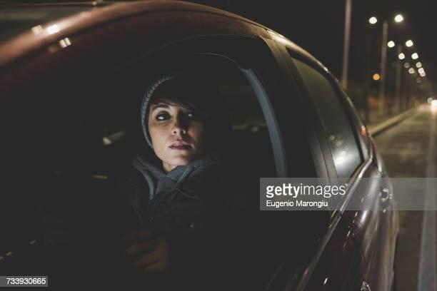 woman looking out of car window on city roadside at night - straßenrand stock-fotos und bilder