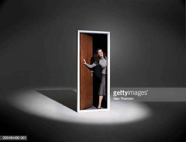 woman looking out of free standing doorway in spotlight - doorway stock pictures, royalty-free photos & images