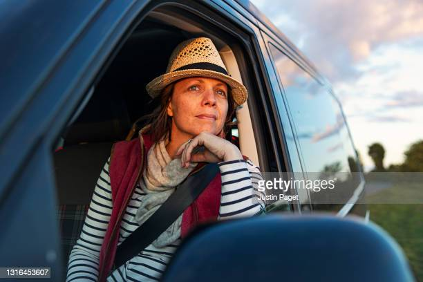 woman looking out of her campervan at sunset - headwear stock pictures, royalty-free photos & images