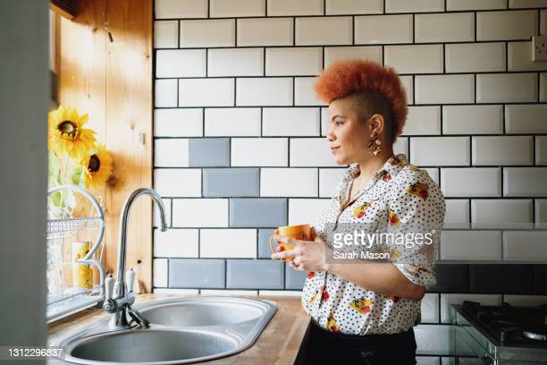woman looking out of kitchen window - one mid adult woman only stock pictures, royalty-free photos & images