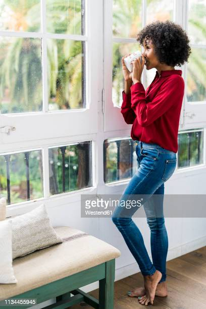 woman looking out of window at home drinking cup of coffee - black blouse stock pictures, royalty-free photos & images