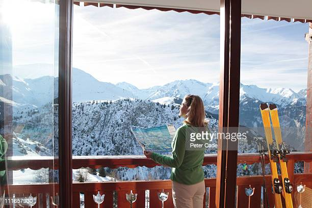 Woman looking out of window at ski slopes