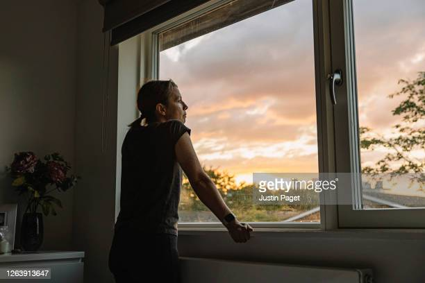 woman looking out of window at sunset - one woman only stock pictures, royalty-free photos & images