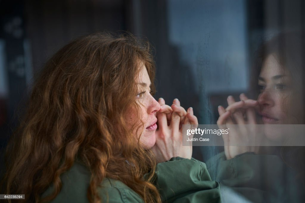 woman looking out of window into her reflection : Stock Photo