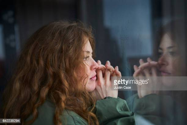 woman looking out of window into her reflection - verdriet stockfoto's en -beelden