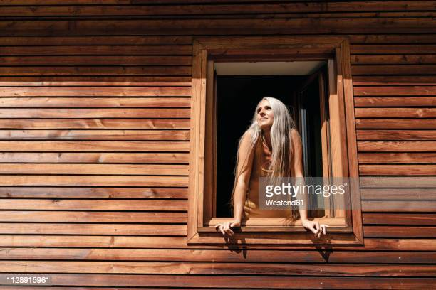 woman looking out of window of her house - leaning stock pictures, royalty-free photos & images