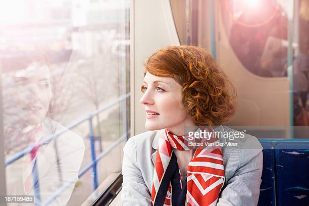 Woman looking out of window of public transport.