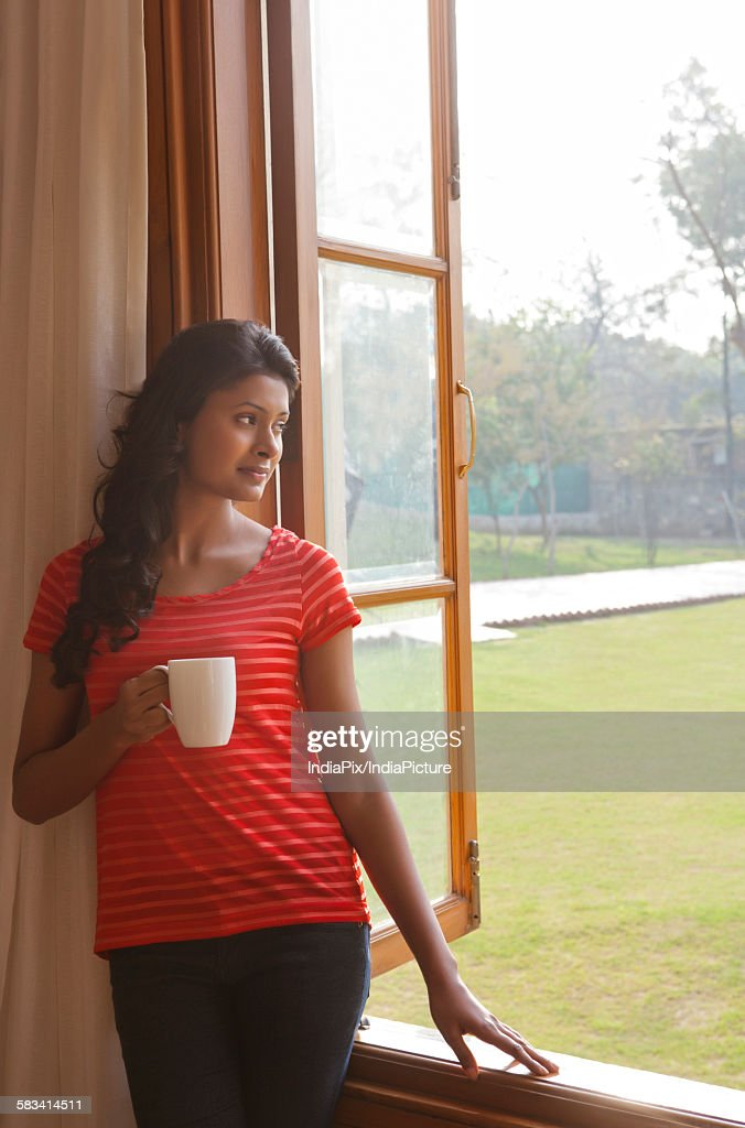Woman looking out of window : Stock Photo
