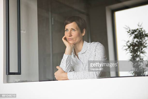woman looking out of window - 顎に手をやる ストックフォトと画像