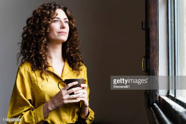 woman looking out of window with coffee cup - one young woman only stock pictures, royalty-free photos & images