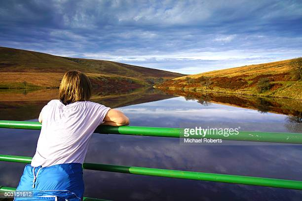 woman looking out over grwyne fawr reservoir in the black mountains, wales - crickhowell foto e immagini stock