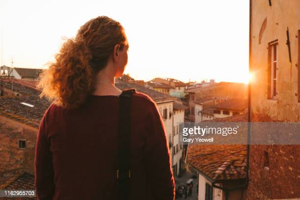 woman looking out over rooftops in san miniato - san miniato stock-fotos und bilder