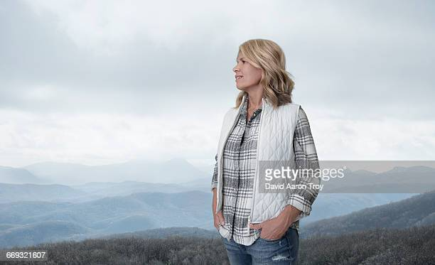 a woman looking out over the mountains - waistcoat stock photos and pictures