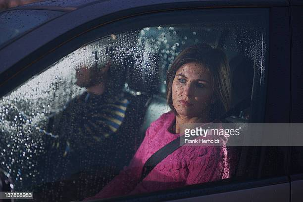 Woman looking out rainy car window