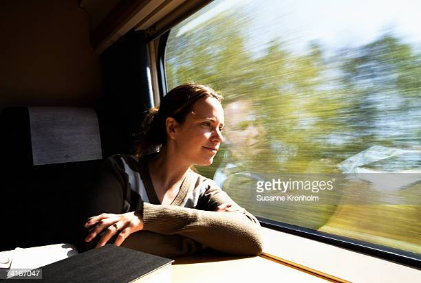 woman looking out the window from a train. - bahnreisender stock-fotos und bilder
