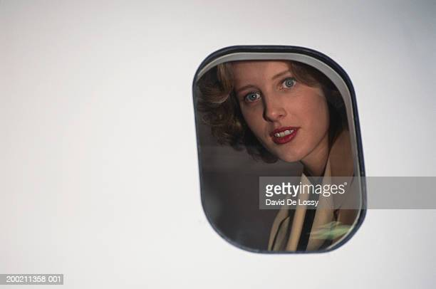 Woman looking out through airplane window, view from outside