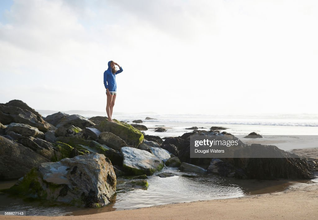 Woman looking out to sea from rocky beach. : Stock Photo