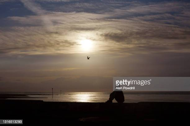 woman looking out to sea in sunset - heaven stock pictures, royalty-free photos & images