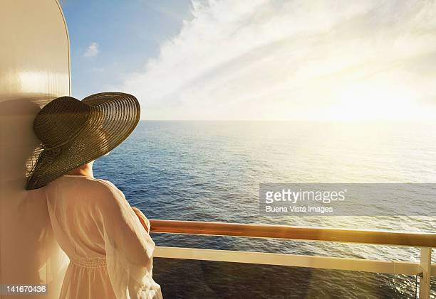 woman looking out to sea on a cruise ship - kreuzfahrtschiff stock-fotos und bilder